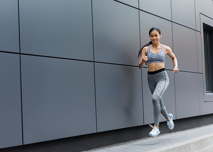 Young woman running for weight loss next to a grey wall