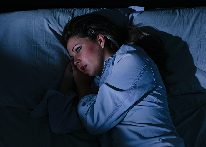 Woman with insomnia lying awake in bed in a dark room.
