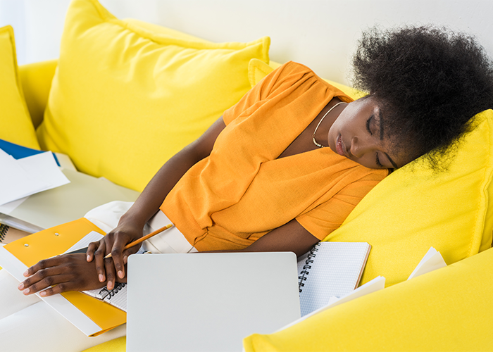 African American woman in yellow top asleep on a yellow couch with open notes, documents, and notepads on her lap.