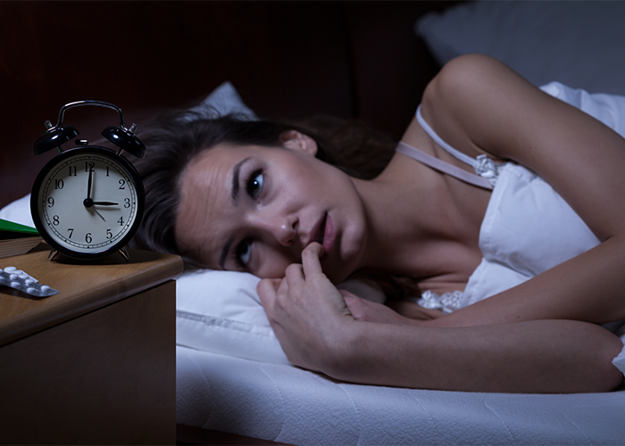Woman with sleep disorder lying awake in bed with her alarm clock showing 3AM.