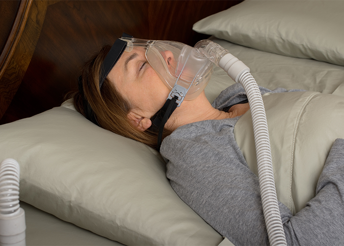 Woman lying in bed sleeping with CPAP machine on.