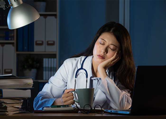 Doctor on shift with her head in her hands and a cup of coffee in the other falling asleep at her desk due to shift work sleep disorder.