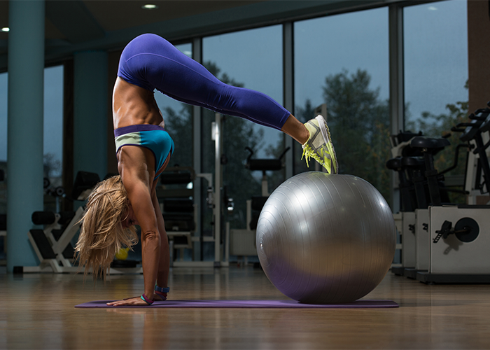 Fit woman on her hands with her feet on an exercise ball for lower back workout.
