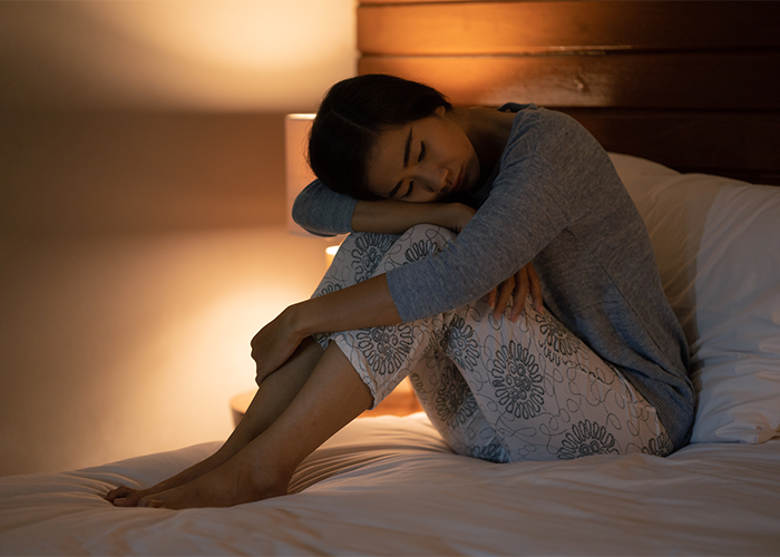 Woman with sleep disorder sitting up in bed at night with lamp on resting her head on her knees.