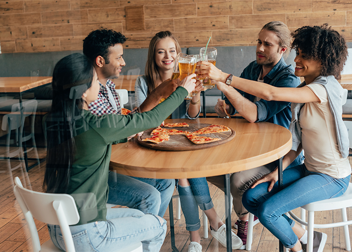 Group of friends in a restaurant having drinks and a pizza