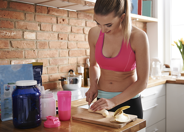 30-year-old woman in fitness gear cutting up a banana
