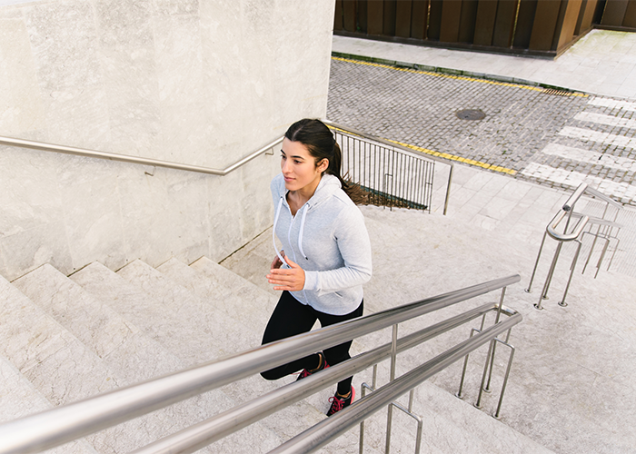 Woman running up stairs for HIIT exercise