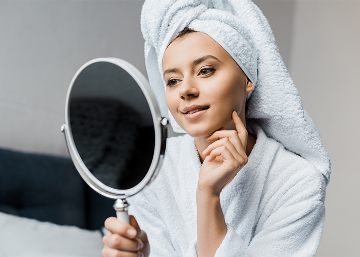 30-year-old woman in a bathrobe looking at her face in a beauty mirror