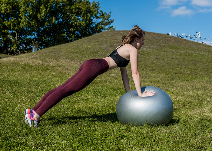 Fit woman doing roll out balance exercises on an exercise ball in a park