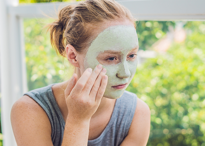 Woman applying green homemade face mask for acne