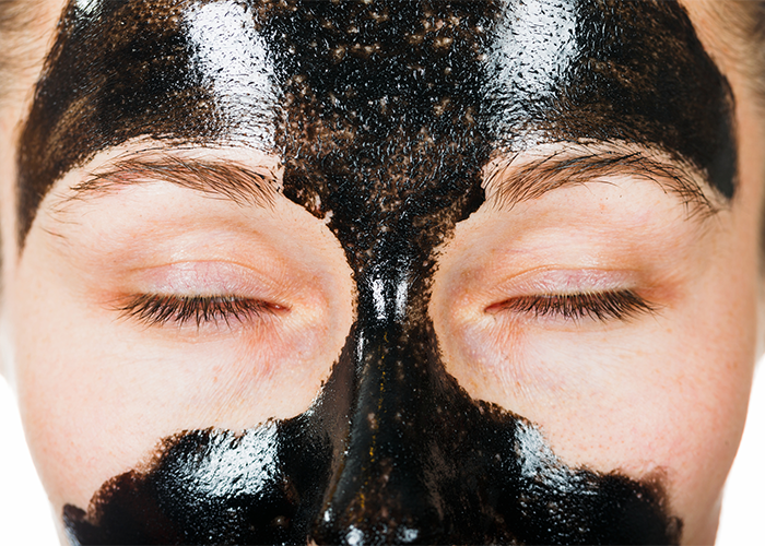 Woman with a black facial mask to remove blackheads from problem areas
