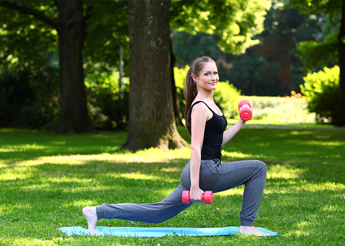 Woman doing weighted lunge calf exercises in the park.