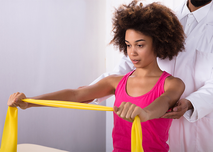 African American woman using resistance band to do shoulder exercises with the help of a physiotherapist