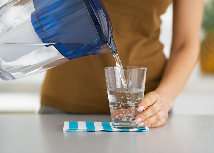 Woman pouring water from a water filter pitcher into a glass