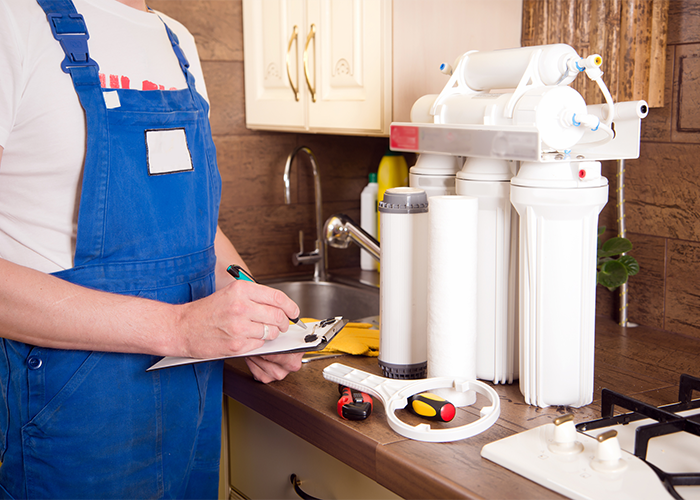 Technician installing a reverse osmosis home system