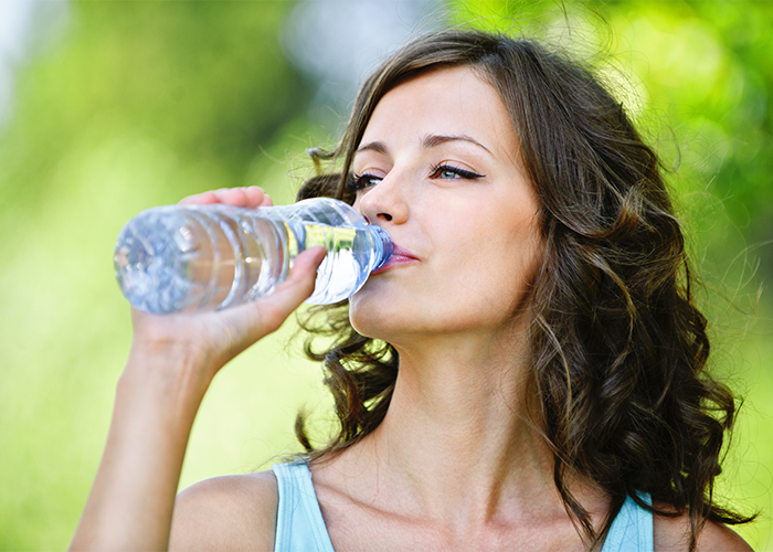 Woman drinking bottled water outdoors