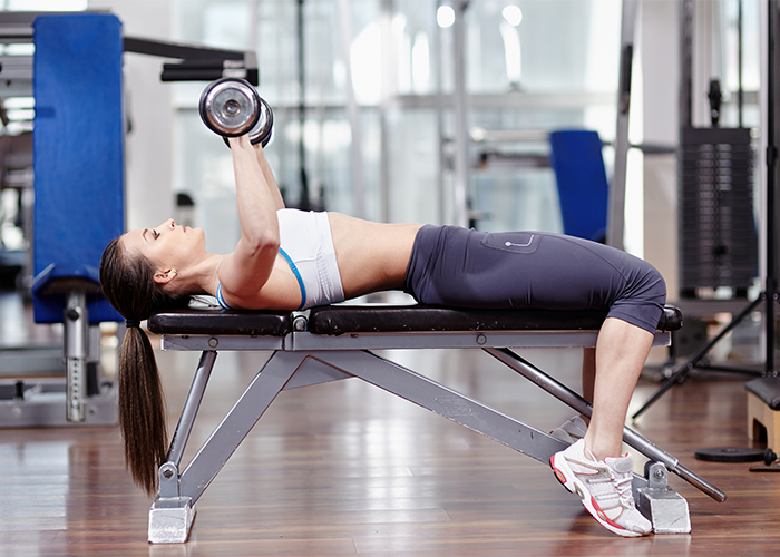 Woman doing skull crushers to work out flabby arms