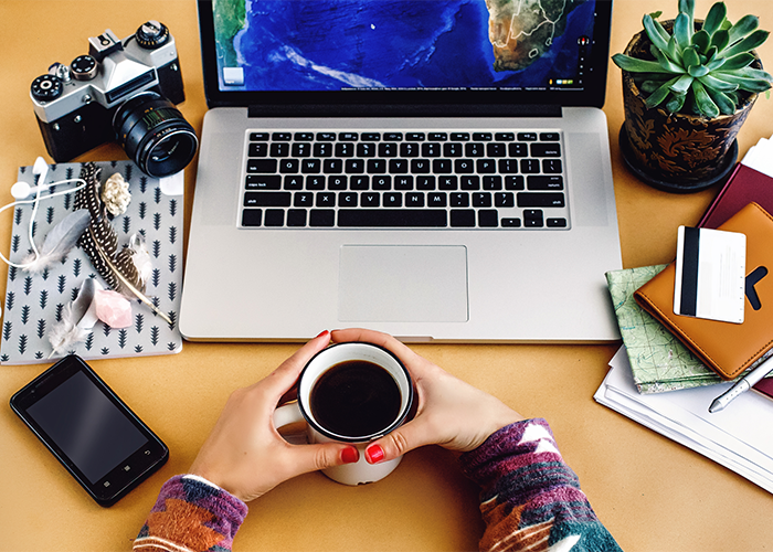 Woman's hands holding onto a cup of coffee with her laptop, camera, phone, a pile of notebooks, and a green plant in front of her