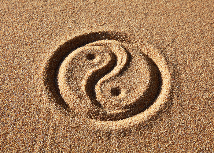 Yin yang symbol drawn in sand