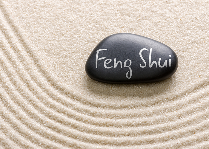 Feng shui written on a black pebble laying on white sand