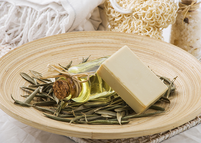 A goat milk soap bar on a bed of dried leaves, next to a bottle of essential oil, in a large dish