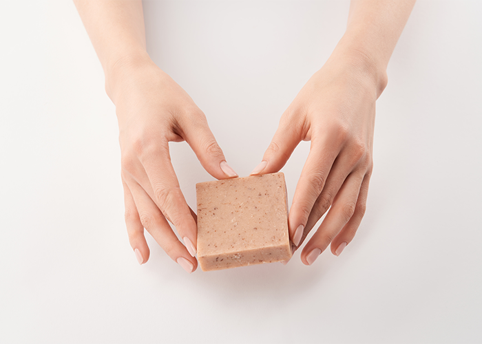 Female hands holding a bar of goat milk soap around the edges