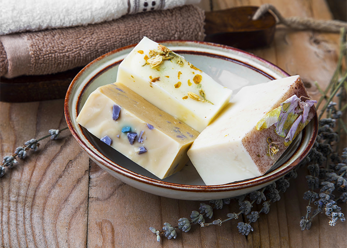 Different goat milk soap bars in a ceramic dish with lavender sprigs around it