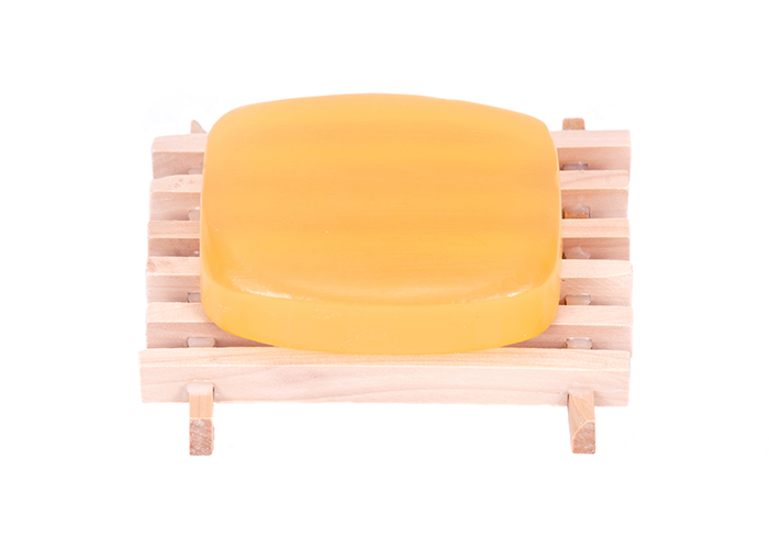 A bar of homemade goat milk soap on a wooden soap dish