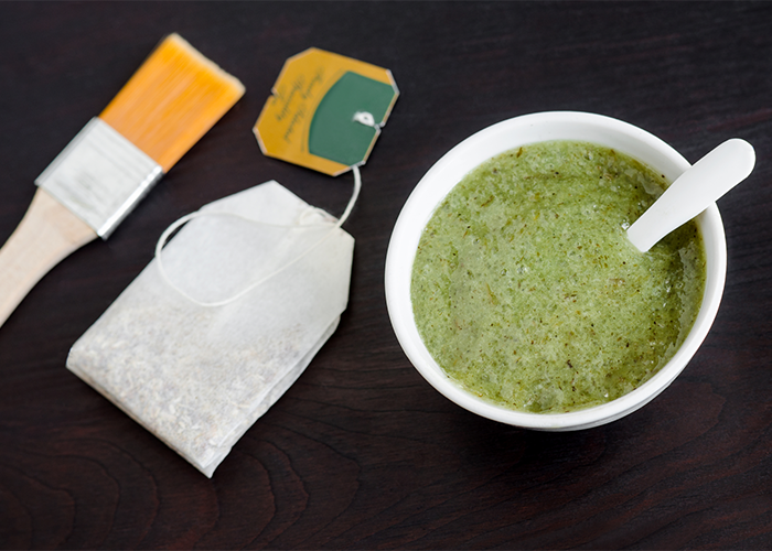 A bowl of green tea with a tea bag next to it as well as a facial brush