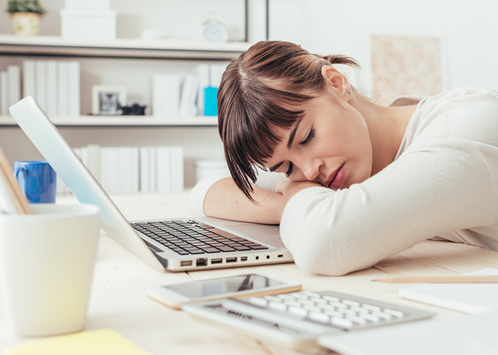 Woman napping in front of her laptop at work
