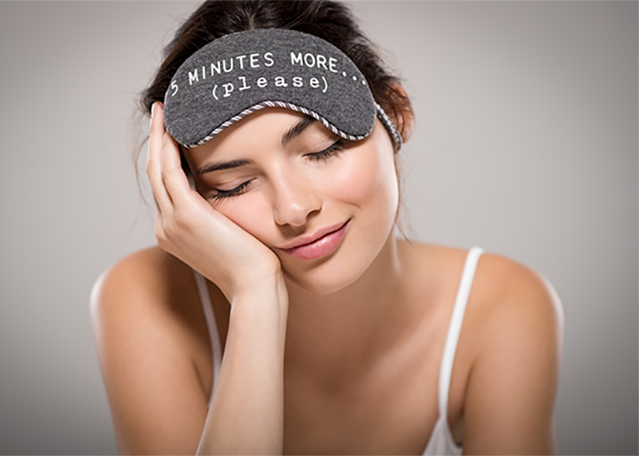 "Woman with eyes closed and an eye mask on her forehead which says ""5 minutes more please"""
