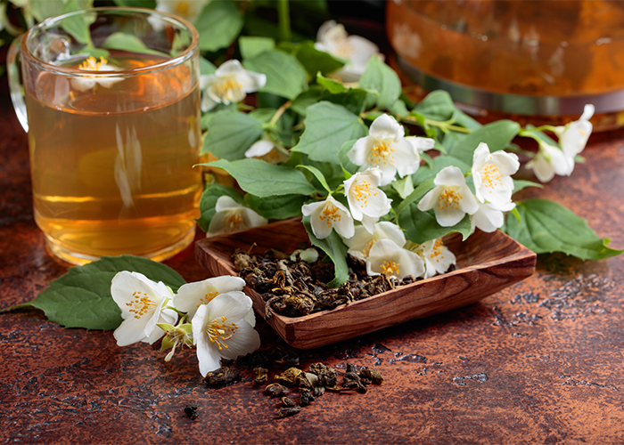Cup of jasmine tea, a brown wooden dish with dried jasmine tea leaves, and fresh jasmine flowers