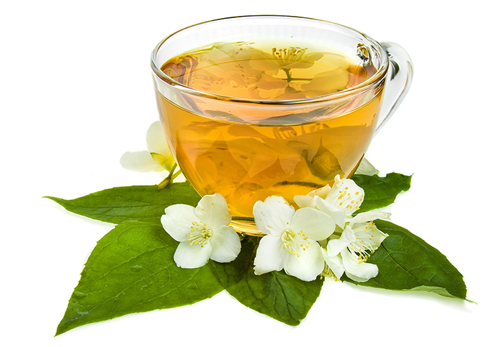 A cup of jasmine tea in a clear teacup laid on green leaves and white jasmine flowers