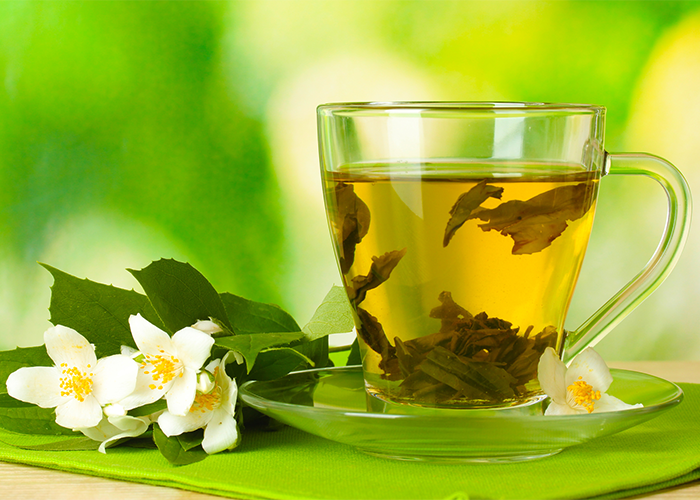 Jasmine tea in a transparent teacup against a green background