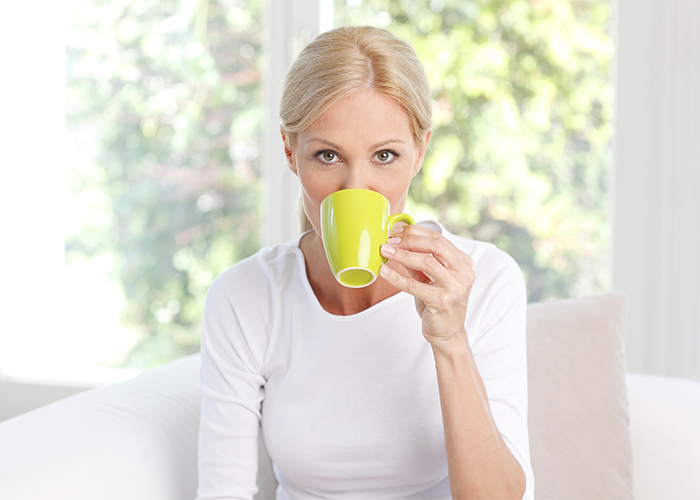 Blonde woman drinking a cup of jasmine tea