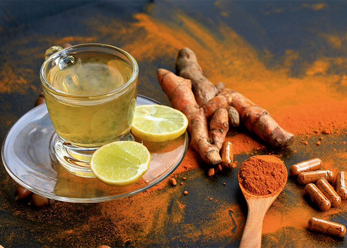 A cup of lemon-cayenne turmeric ginger tea in a transparent teacup and saucer, with fresh turmeric root and turmeric powder on the table next to it