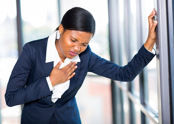 Woman in formal office suite holding her chest in pain