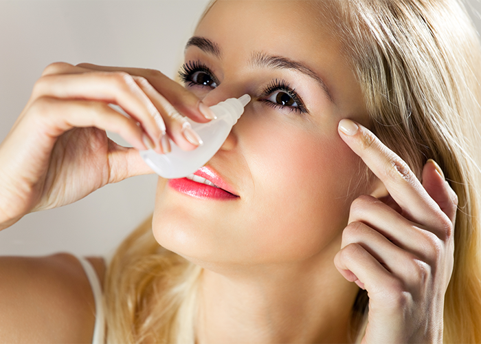 Woman putting eye drops in her dry eyes