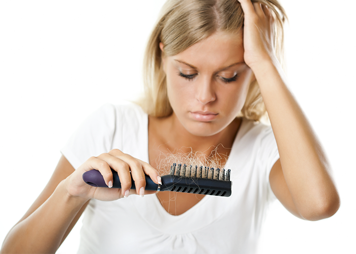 Woman with hair loss looking at her hairbrush with lots of hair in it