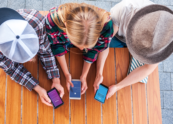 top down view of three friends using social media on their cellphones