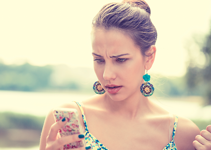woman looking at her phone in frustration