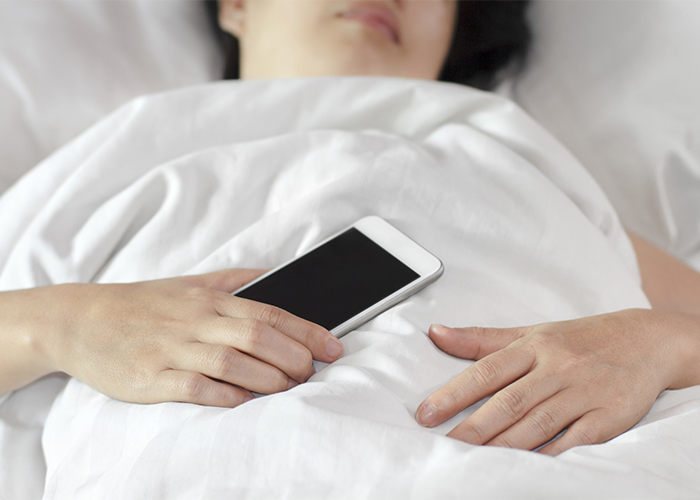 woman asleep in bed holding her smartphone in her hand