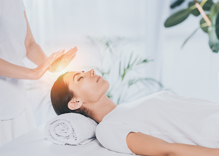 Woman laying down receiving reiki healing therapy