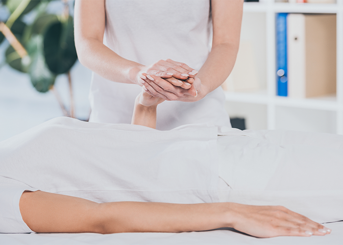 Reiki practitioner holding a patient's hand to perform reiki healing