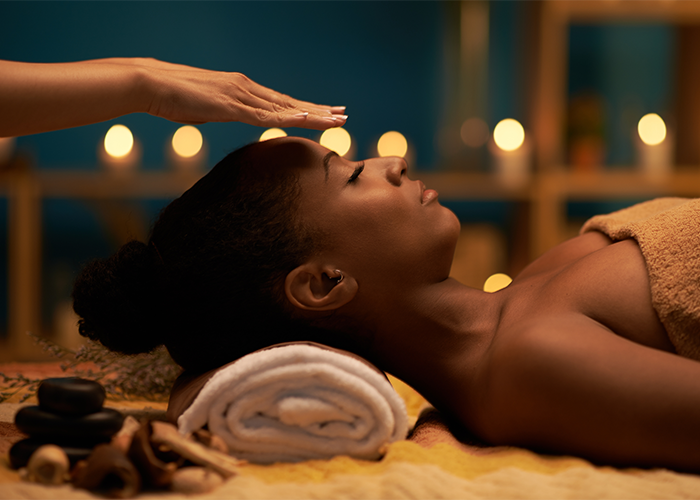 African American woman with eyes closed receiving reiki healing from a practitioner whose hands are floating above her forehead