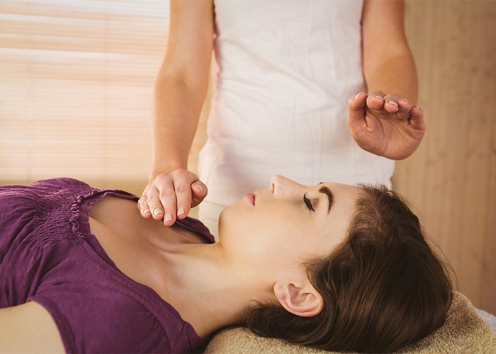 Woman receiving reiki healing