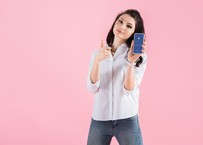young woman holding a smartphone showing facebook and with her thumbs up