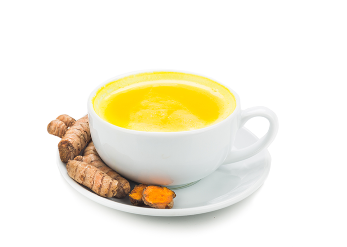 Turmeric tea in a white cup on a white saucer with turmeric root on the side