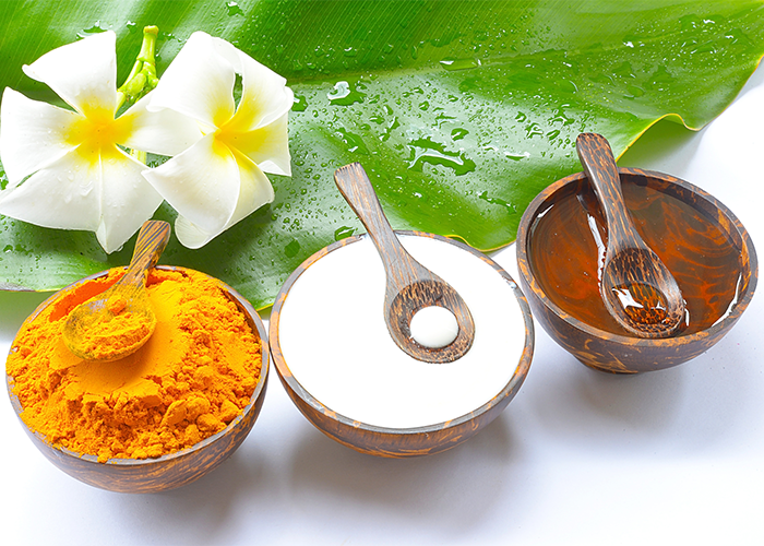 Turmeric powder, yogurt, and honey in wooden bowls with wooden spoons and a large green leaf and white flowers in the background