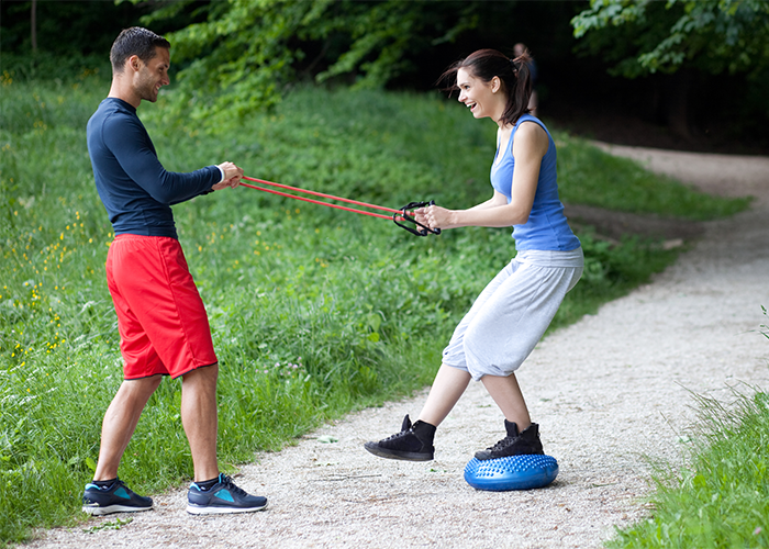 Woman working with a male coach in the park on balance exercises